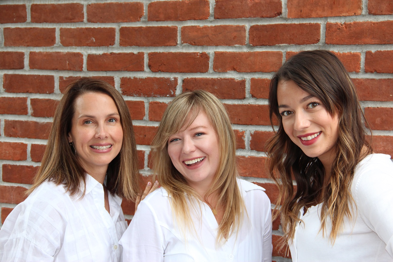 A Better Alteration staff standing in front of a brick wall.