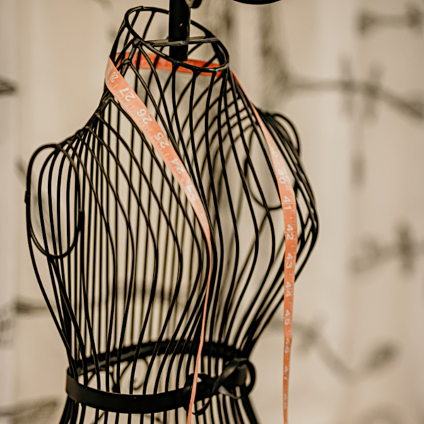 A wire dress-form, draped with a fabric tape measure.