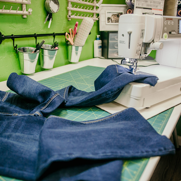 Hemming a pair of jeans with a sewing machine.
