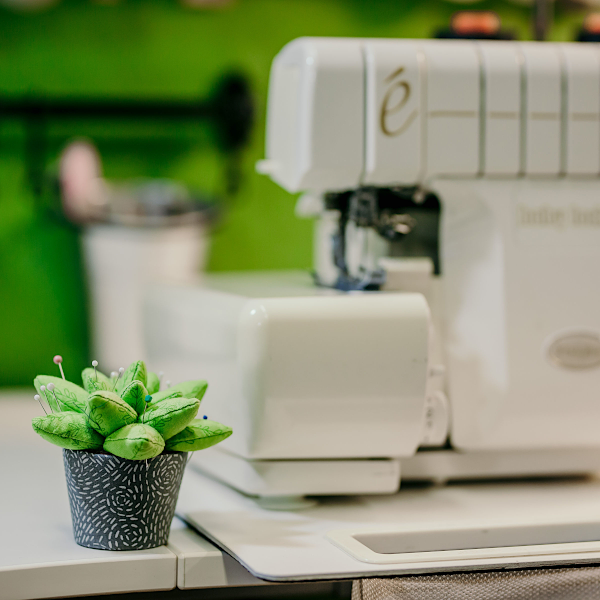 A white sewing machine and a green pin cushion.